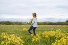 Girl Walking With Bouquet Of Rape Flowers On Rape Field
