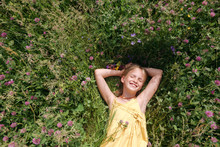Portrait Of Happy Little Girl With Eyes Closed Lying On A Meadow In Summer