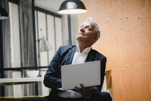 Senior Businessman Sitting Under Ceiling Lamp, Using Laptop, Looking Into The Light