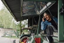 Senior Man On The Phone On A Tractor On A Farm