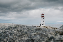 Peggys Point Lighthouse On Rock Formation By Sea Against Cloudy Sky, Nova Scotia, Canada