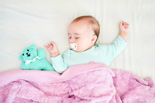 Portrait Of Sleeping Baby Girl With Pacifier And Cuddly Toy