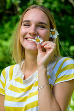 Close-up Of Smiling Beautiful Woman Holding Oxeye Daisies In Park