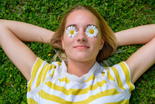 Close-up Of Young Woman With Oxeye Daisies On Eyes Lying Over Grassy Land In Park