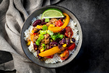 Bowl Of Mexican Rice With Bell Peppers, Tofu, Kidney Beans, Tomatoes, Corn, Lime And Scallion