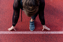 Athletic Woman At Starting Line On Tartan Track, From Above