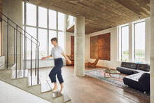 Woman Walking Up Stairs In A Loft Flat