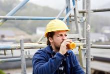 Worker Drinking Juice On Scaff...