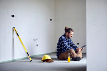 Worker On A Construction Site Sitting On The Floor Using Tablet