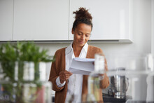 Portrait Of Smiling Businesswoman Standing In Kitchen Looking At Contract