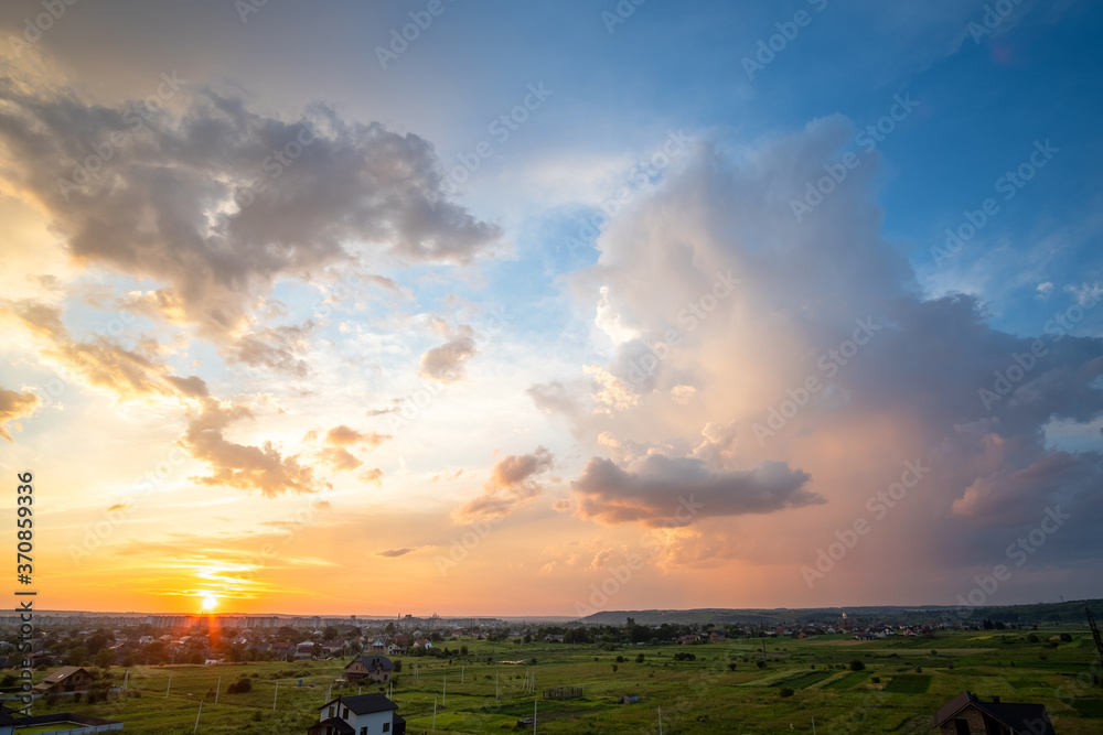 Fototapeta Dramatic sunset over rural area with stormy clouds lit by orange setting sun and blue sky.