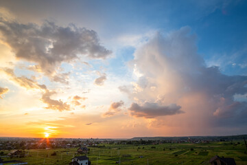 Dramatic sunset over rural area with stormy clouds lit by orange setting sun and blue sky.