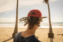 Costa Rica, Puntarenas Province, Puntarenas, Rear View Of Young Man Wearing Dreadlocks Looking At Ocean From Playa Santa Teresa
