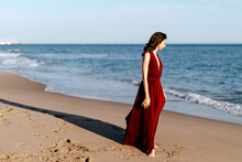 Delicate Woman In Red Dress Walking At The Sea, Feeling The Sun