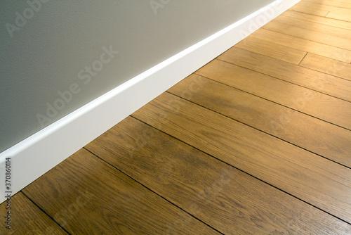 Photo Close up of white plastic plinths on dark wooden oak floor parquet