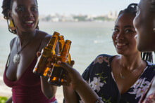 Smiling Young Female Friends Toasting Beer Bottles In Balcony