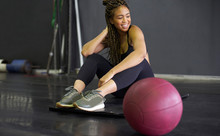 Smiling Young Woman With Braided Hair Sitting On Mat In Gym