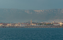 View Of Split, Croatia Town From A Car Ferry Approaching For Very Far. Church Belltower Seen Rising Above The Old Buildings, Mountains And Sky In The Distance