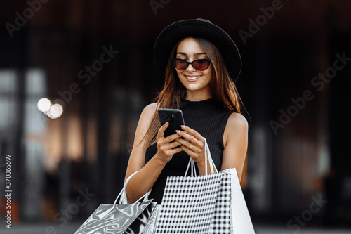 Fotografía Happy beautiful elegant girl in a black dress and hat, using a mobile phone, holding shopping bags