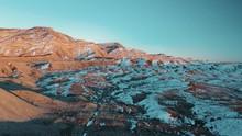 Aerial Desert Sunset Over Mountain Range And Sand Ridges