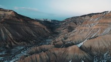 Flying Into Dramatic Desert Mountain Canyon With A Fresh Layer Of Snow At Sunset