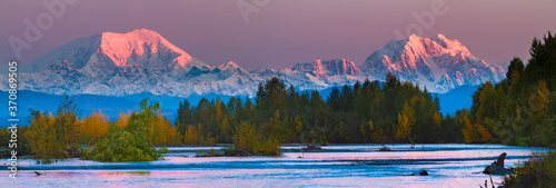 Fototapeta Sunrise on Mt Foraker and Mt Hunter accross the Susitna river with fall foliage.  Mount Foraker is a 17,400-foot mountain in the central Alaska Range, in Denali National Park obraz