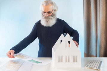 Old man works as architect. Elderly man next to layout of house. Old man holds construction drawings in his hands. Drawings of house in hands of architect. Concept - experienced architect. Gray beard