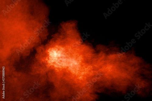 Fotografía Abstract explosion of orange dust on black background