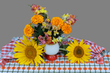 Against A Gray Background, On A Napkin In A Vase, There Is A Bouquet Of Tagetis And Snapdragon Flowers, Next To A Sunflower.
