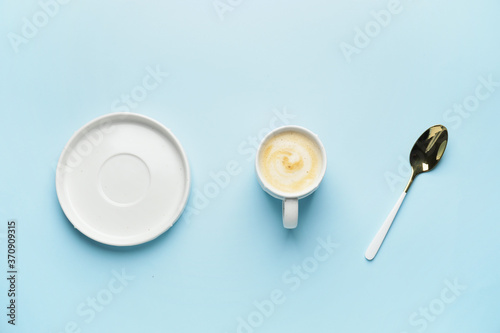 Cup of hot coffee with saucer and spoon on color background Fototapeta