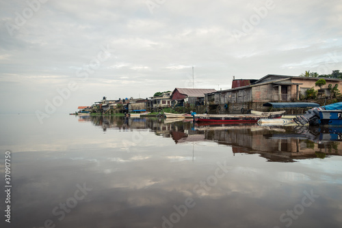 Photographie houses and pier reflected in the calm waters of the San Juan de Nicaragua River