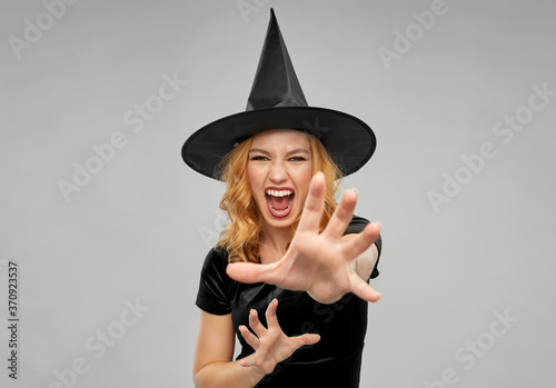 Canvas holiday, theme party and black magic concept - scary woman in halloween costume