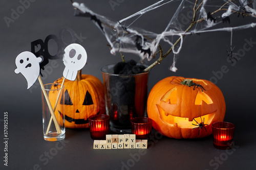autumn holidays and decorations concept - wooden toy blocks with happy halloween letters, jack-o-lanterns or carved pumpkins, burning candles and spiders on spiderweb