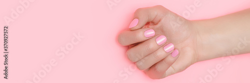 Photo Beautiful female hand with perfect pink nails polish on pink background