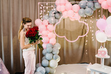 Portrait Lady Holding Bouqet Flowers On Background Grey And Pink Balloons. Beautiful Happy Young Woman On Birthday Holiday Party.