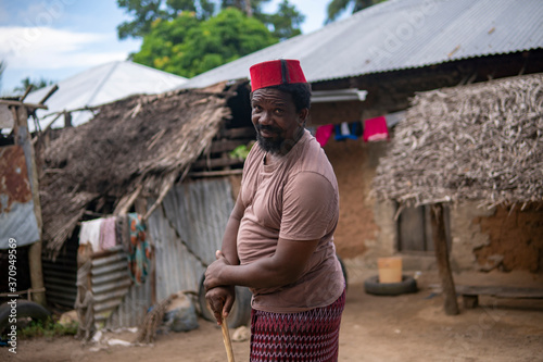 Fotografía An African Older Man in Red Muslim Taqiyyah Fez Hat posing with a stick for lame