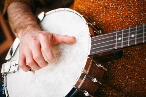 Photo Close up of a Male Banjo player relaxing on the porch, practicing and picking aw