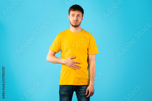 Fototapeta Young male model touching his stomach at studio