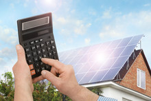 Man Using Calculator Against House With Installed Solar Panels. Renewable Energy And Money Saving