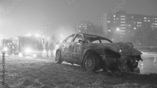 Winter car accident, burned car with fire engine and buildings in the background Canvas Print