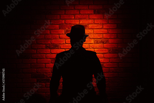 Fototapeta Silhouette of a man in a hat on a brick background
