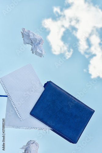 Fototapeta Diary and crumpled sheets of paper in the air against the background of a blue sky with clouds. obraz na płótnie