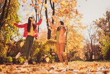 Full Length Body Size View Of Two Nice Attractive Glad Carefree Excited Cheerful Cheery Best Girlfriends Spending Weekend Pastime Outdoor Having Fun Throwing Yellow Tree Leaves Fooling