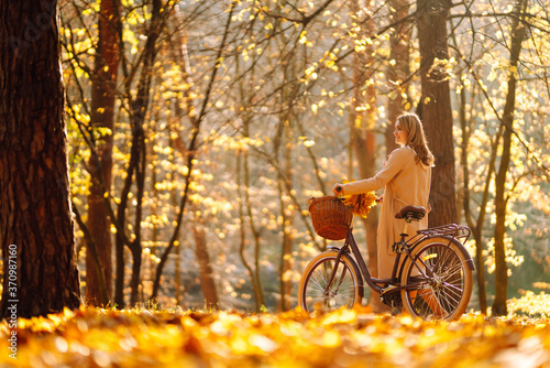 Fototapeta Stylish woman with a bicycle enjoying autumn weather in the park. Beautiful Woman walking  in the autumn forest. obraz na płótnie