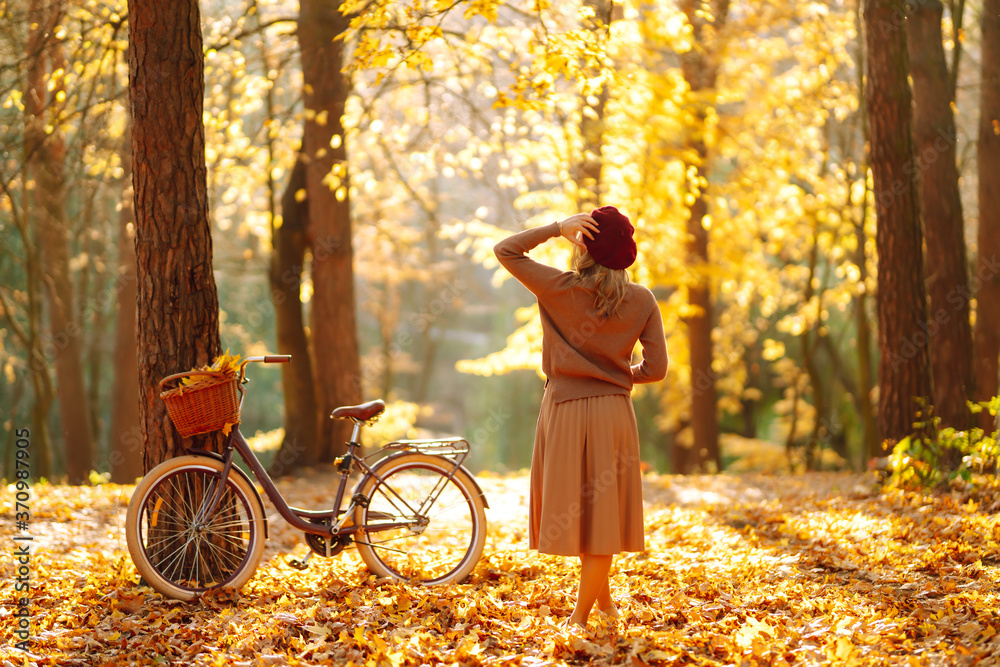 Fototapeta Stylish woman with a bicycle enjoying autumn weather in the park. Beautiful Woman walking  in the autumn forest. - obraz na płótnie
