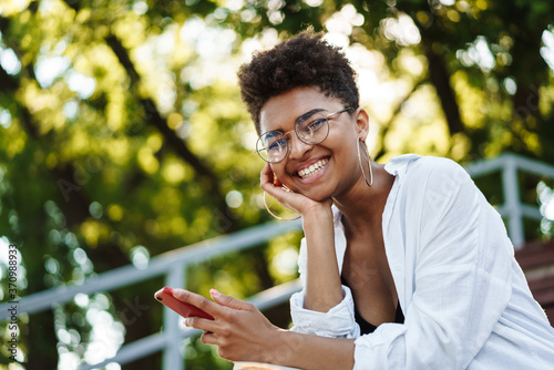 Fototapeta Woman sitting outdoors in park chatting by mobile phone obraz