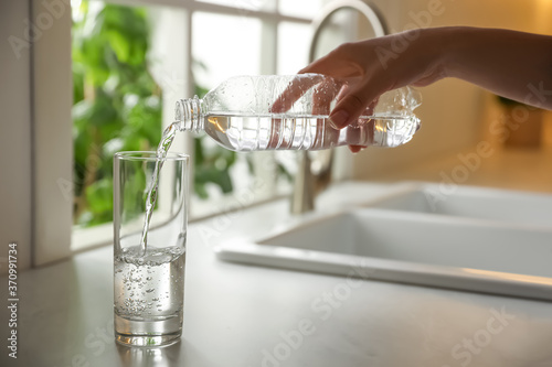 Valokuvatapetti Woman pouring water from bottle into glass in kitchen, closeup