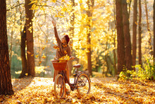 Stylish Woman With A Bicycle Enjoying Autumn Weather In The Park. Beautiful Woman Walking  In The Autumn Forest.