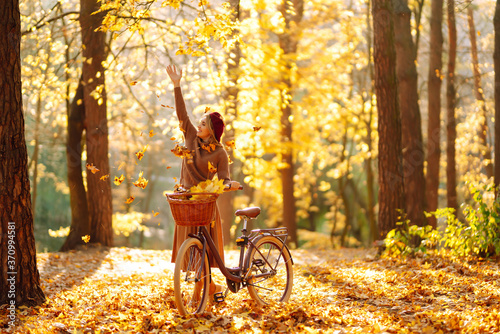 Fototapeta Stylish woman with a bicycle enjoying autumn weather in the park. Beautiful Woman walking  in the autumn forest. obraz