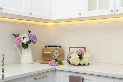 Beautiful hydrangea flowers and radio set on light countertop Fototapeta